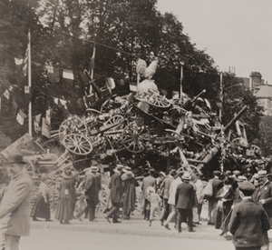 View of civilians in front of a large pile of captured German small artillery covered with wreathes, topped with a statue of an oversized rooster and flags from different countries hanging behind, 1919