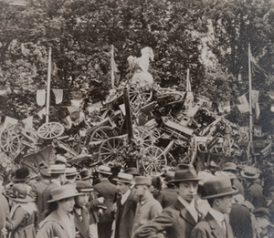 Close-up view of civilians in front of a large pile of captured German small artillery covered with wreathes, topped with a statue of an oversized rooster and flags from different countries hanging behind, 1919