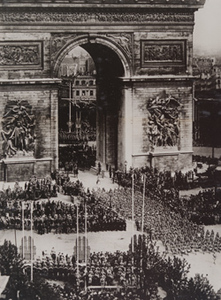 French military band marching under the Arc de Triomphe with military formations around the Arc and civilians crowding the flag-lined streets, July 14, 1919, Paris