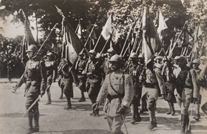 Street-level view of French soldiers marching with battle flags