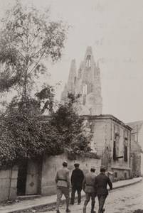 3 soldiers and one civilian walk along a street in the town of Soissons, a damaged church steeple in the background