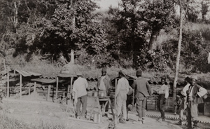 View of an outdoor kitchen of an Algerian(?) camp, men standing on line for food