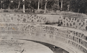 View of a soldier standing in a large stone and concrete circular German gun emplacement