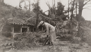 Red Cross worker [Elsa Bowman] picks up some debris in front of a hillside dugout, Pinon