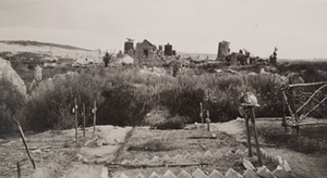 Eight wooden crosses marking graves, one with a helmet hung on it and a destroyed stone building in the background, Berry-au-Bac