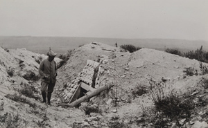 Soldier standing in front of an abandoned dugout entrance, flat fields in the background, Craonne