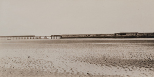 View of an expanse of mudflats, a viaduct in the distance, port of Zeebrugge, Belgium