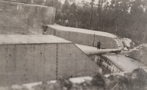 Close-up of a large German gun turret in a circular concrete enclosure with two men standing next to it for scale