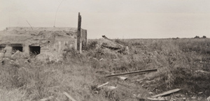 View of a damaged concrete fortification in a grassy field