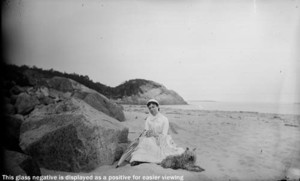 Mrs. Jim Scott and dog seated by rock at east end of Singing Beach, Manchester