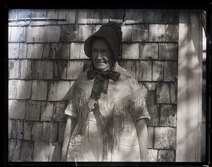 Abbie Loring in Quaker attire, posed in front of shake-sided house