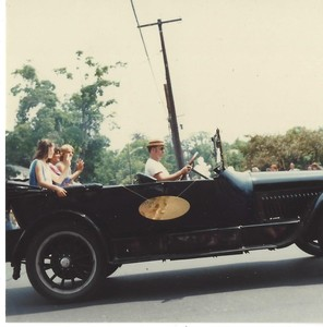Unknown people riding a in classic black car in the Town of Plainville 75th Anniversary Diamond Jubilee parade