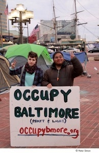 Occupy Baltimore: two demonstrators flashing the peace sign and posing behind 'Occupy Baltimore' sign