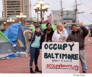 Occupy Baltimore: four demonstrators posing behind 'Occupy Baltimore' sign