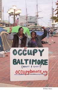 Occupy Baltimore: two women posing with raised fist and peace sign behind 'Occupy Baltimore' sign