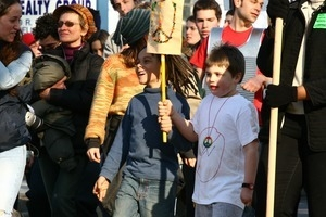 Children in the crowd, holding sign decorated with a peace symbol: rally and march against the Iraq War