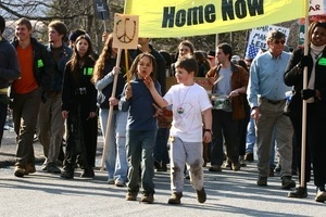 Children at the head of the march with a sign decorated with a peace symbol: rally and march against the Iraq War