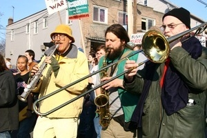 Brass band playing among anti-war marchers: rally and march against the Iraq War