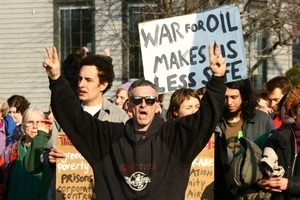 Anti-war marcher in the crowd flashing peace signs: rally and march against the Iraq War