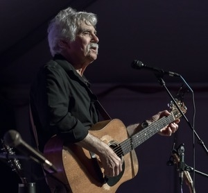 Tom Rush playing acoustic guitar in concert at the Payomet Performing Arts Center