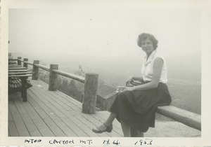 Bernice Kahn seated on fence on top of Cannon Mountain