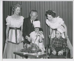 Abe Stark and two performers carving turkey with young clients
