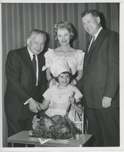 Abe Stark, Candace Hilligoss and Willis C. Gorthy carving a turkey with young client.
