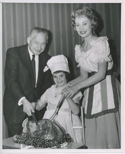 Abe Stark and Candace Hilligoss carving turkey with young client