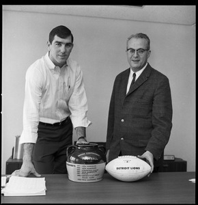 Greg Landry (UMass Amherst football quarterback) shaking hands with University of Massachusetts President John W. Lederle, with ceremonial football and Yankee Conference Trophy
