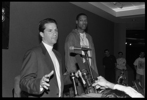 John Calipari at the microphone during a press conference with Marcus Camby (background)