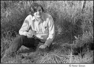 Joe Pilati in tall grass, holding a book and looking at a puppy, Packer Corners commune