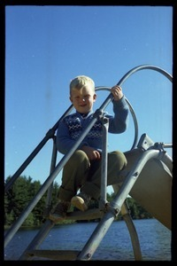 Boy seated atop a slide, Pine Beach
