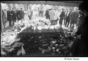 Jack Kerouac's funeral: view of casket at the cemetery, Gregory Corso holding rose (right)
