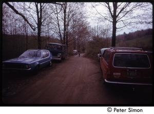 Cars parked along a dirt road, Tree Frog Farm commune