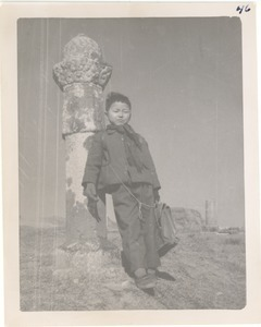 Boy with stone pillar at burial site