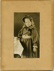 Alice Channing: portrait as a young girl, standing next to table