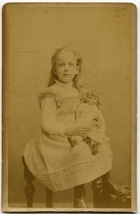 Alice Channing: studio portrait as a young girl, seated with doll