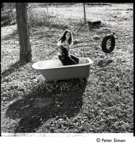 Jenny Rose seated in a tub outdoors with dog and tire swing, Tree Frog Farm Commune