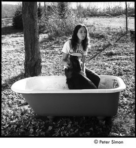 Jenny Rose seated in a tub outdoors with dog, Tree Frog Farm Commune