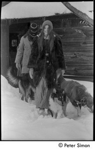 Catherine Blinder in heavy winter coat, with masked communard [Elliot Blinder] and dogs, walking in heavy snow, Tree Frog Farm commune