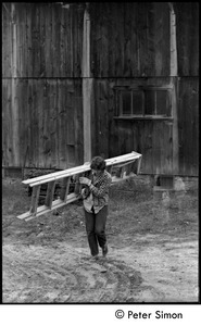 Laura Bradley carrying a ladder past the barn, Montague Farm commune