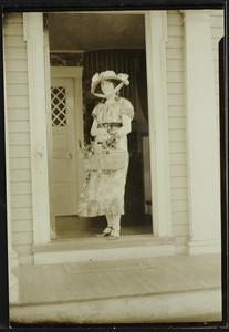 Woman stands in the doorway of a house, location unknown, undated