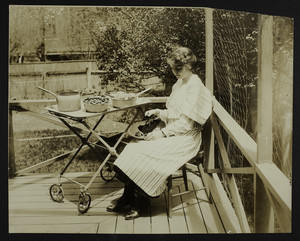 Woman on a patio with a tea wagon, location unknown, undated