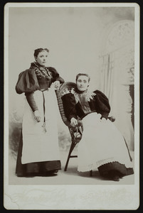 Two unidentified women, one seated and one standing, full length, facing front, location unknown, undated