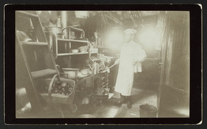 Man standing in a kitchen on Yacht Cora, location unknown, undated