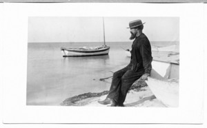 Captain Thomas Sandsbury near the shore with his boat, Tuckernuck Island, Mass., undated