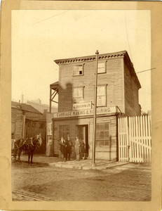 Men on the sidewalk in front of J. Brown, Jr.'s Carriage Making & Repairing shop, 477 Washington Street, Boston, Mass., ca. 1889