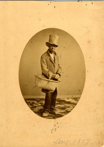 Studio portrait of a man in a stove pipe hat and with a basket, Aug. 1859