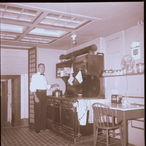 Man putting kettle on stove, kitchen, Beauport, Sleeper-McCann House, Gloucester, Mass.