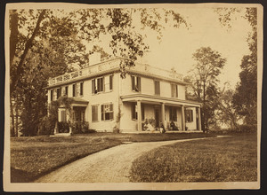 Exterior view of the Quincy House with family seated on porch